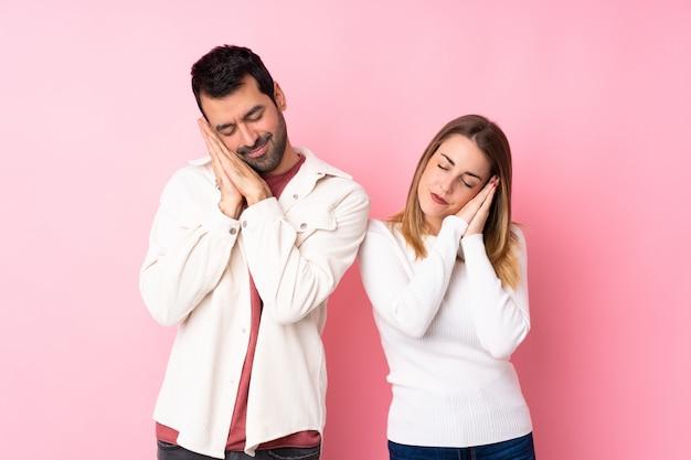 Casal no dia dos namorados sobre parede rosa isolada, fazendo o gesto do sono em expressão dorable