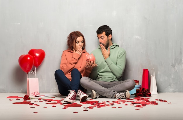 Casal no dia dos namorados surpreendeu enquanto segura um piggybank
