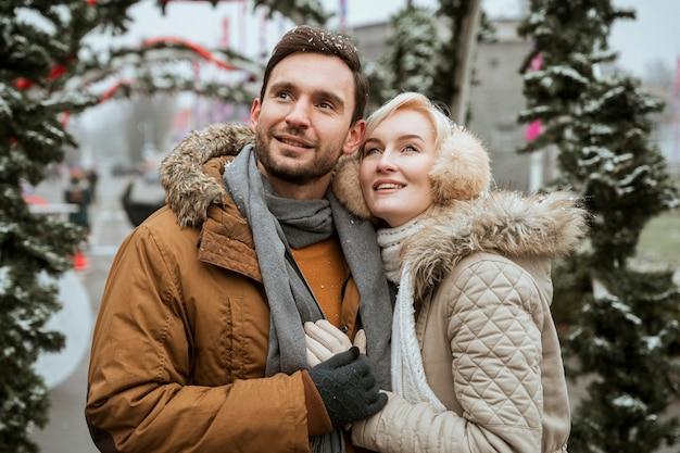 Casal no inverno abraçando tiro médio