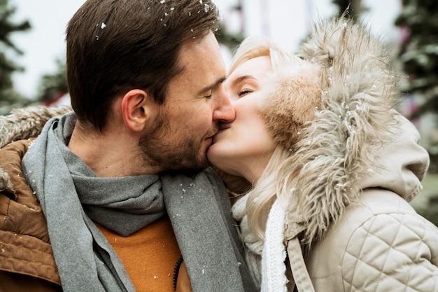 Casal no inverno beijando close-up