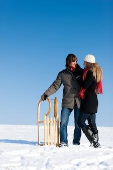 Casal no inverno com trenó