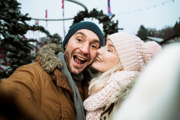 Casal no inverno dando um beijo