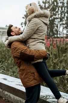 Casal no inverno se abraçando ao ar livre