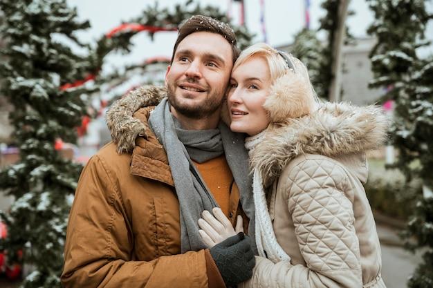 Casal no inverno se abraçando e olhando para longe