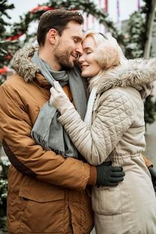 Casal no inverno se abraçando e sendo feliz