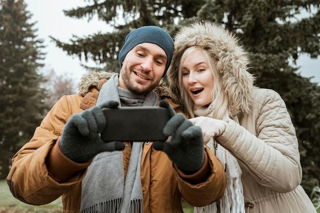Casal no inverno tirando uma selfie vista frontal