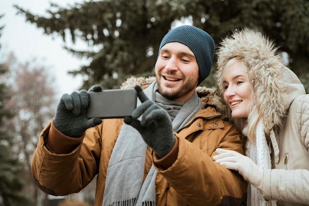 Casal no inverno tirando uma selfie