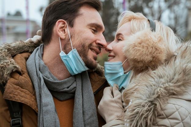 Casal no inverno usando máscaras médicas