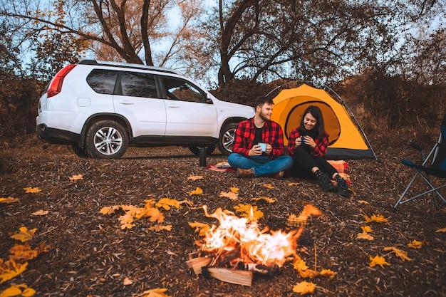 Casal no local de acampamento sentado perto da barraca da fogueira e o carro no fundo