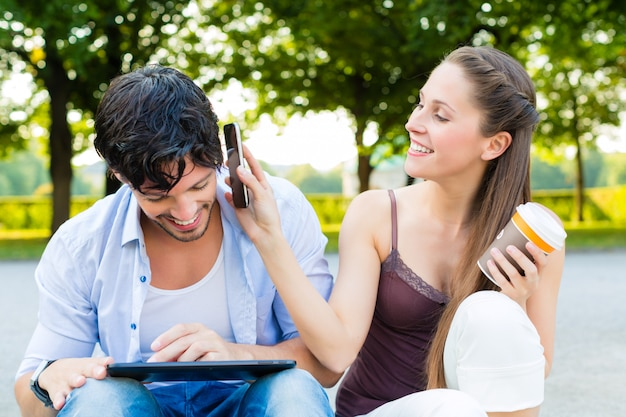 Casal no parque da cidade com computador tablet