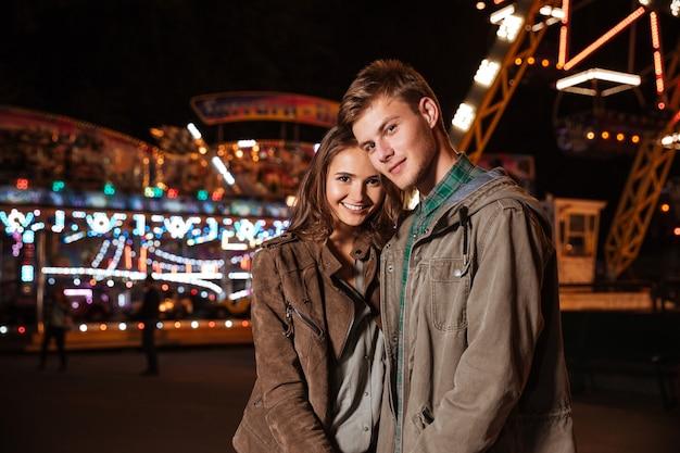 Casal no parque de diversões, olhando para a câmera.
