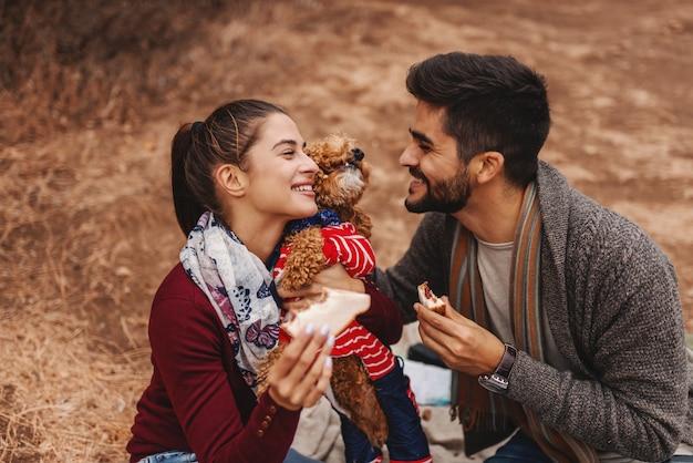 Casal no piquenique, sentado no cobertor e brincando com o cachorro. homem segurando o biscoito enquanto mulher abraçando o cachorro. tempo de outono.