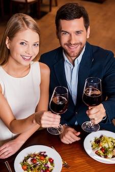 Casal no restaurante. vista superior de um belo jovem casal apaixonado brindando com vinho tinto enquanto estão sentados juntos no restaurante