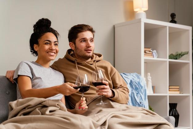 Casal no sofá assistindo tv e bebendo vinho