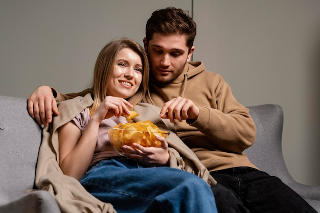 Casal no sofá assistindo tv e comendo batatinhas