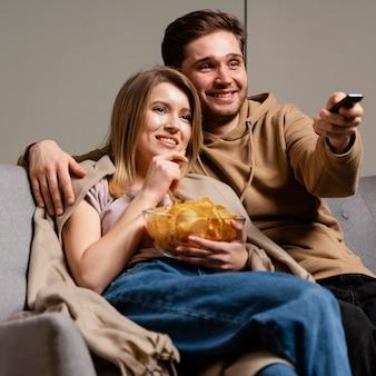 Casal no sofá assistindo tv e comendo batatinhas Foto gratuita
