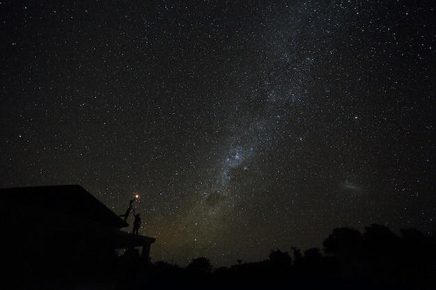 Casal no telhado assistindo mliky maneira e estrelas no céu noturno na ilha de bali.
