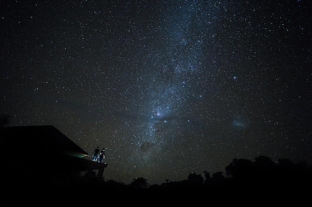 Casal no telhado assistindo mliky maneira e estrelas no céu noturno