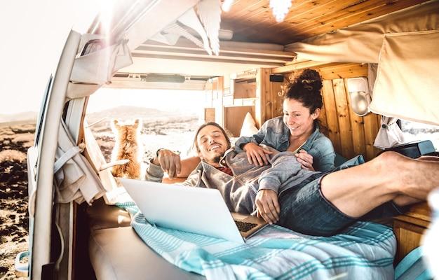 Casal nômade digital viajando junto com um cachorro em um transporte de van retrô - conceito de estilo de vida de liberdade com pessoas indie em uma aventura de minivan compartilhando conteúdo usando notebook - filtro de luz de fundo quente