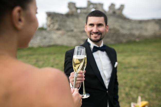 Casal nupcial brindando com taças de champanhe na natureza Foto Premium
