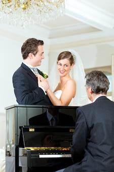 Casal nupcial na frente de um piano