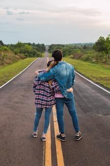 Casal observando a estrada. jovem casal atraente romântico observando o caminho