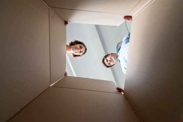 Casal olhando dentro de uma caixa vazia enquanto faz as malas para se mover