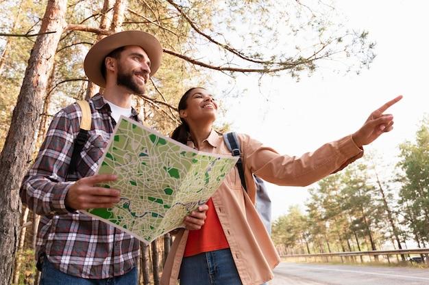 Casal olhando nas mesmas direções enquanto o homem segura um mapa