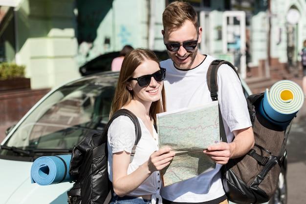 Casal olhando o mapa enquanto viaja