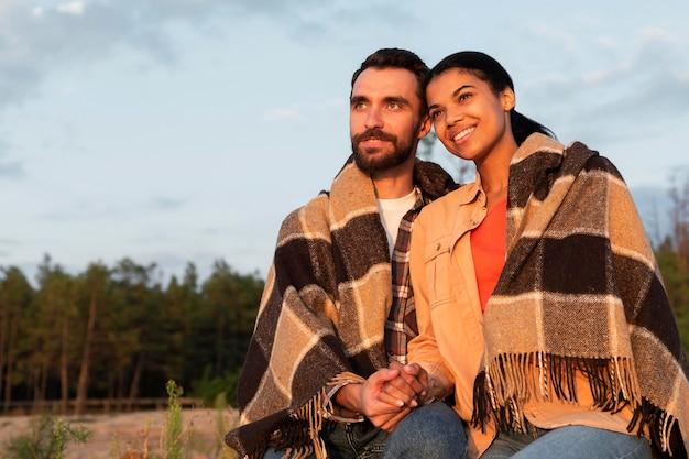 Casal olhando o pôr do sol enquanto é coberto por um cobertor