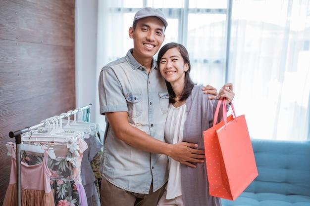 Casal olhando para a câmera segurando um saco de papel em uma pequena butique