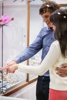Casal olhando para a exibição de relógios de pulso