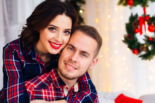 Casal olhando para a lente da câmera e sorrindo; eles estão sentados em uma cama com enfeites de natal