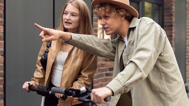 Casal olhando para algo na cidade enquanto andava de scooters elétricos
