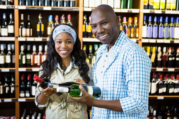 Casal olhando para garrafa de vinho na seção de compras no supermercado