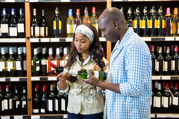 Casal olhando para garrafa de vinho na seção de compras