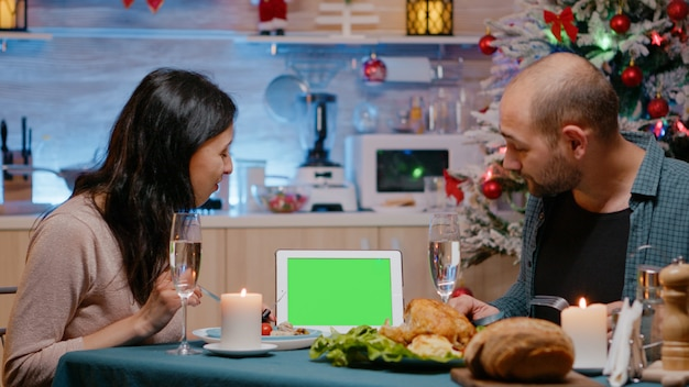 Casal olhando para tela verde horizontal no tablet