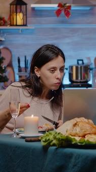 Casal olhando para um laptop e comendo uma refeição festiva