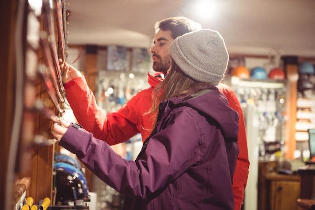 Casal olhando para um poste de esqui em uma loja