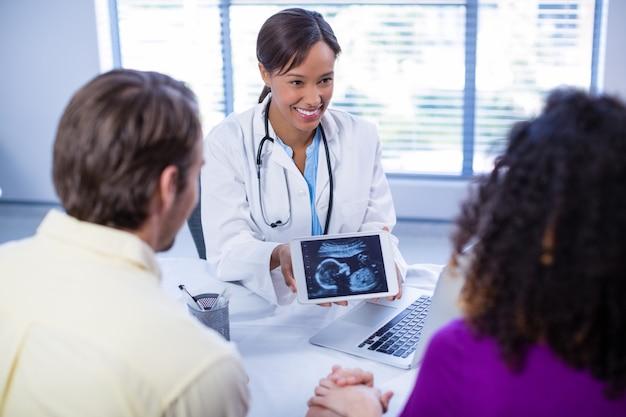 Casal olhando ultrassonografia de bebês no tablet digital de médicos