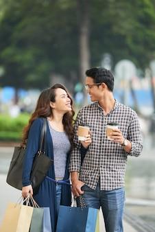 Casal olhando um ao outro com amor segurando sacolas de compras