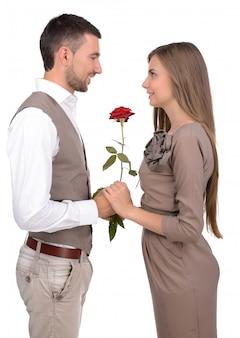 Casal olhando um ao outro e segurando um rosas vermelhas.