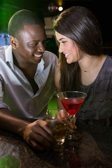 Casal olhando um ao outro e sorrindo enquanto toma bebidas no bar
