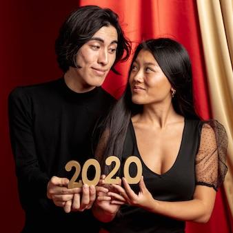 Casal olhando um ao outro segurando placa de ano novo
