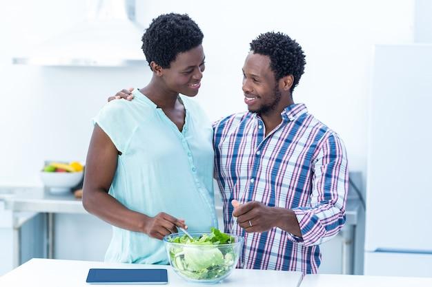 Casal olhando um para o outro enquanto tomam salada