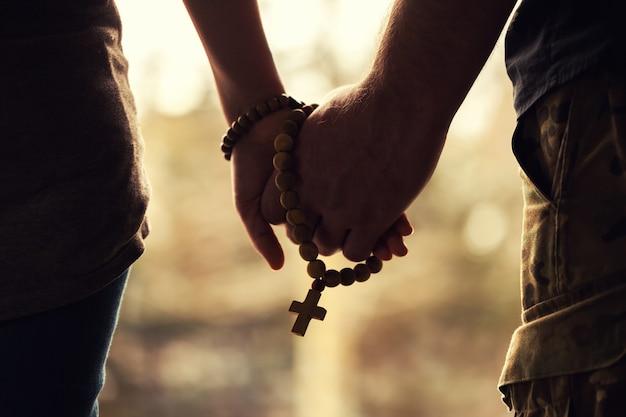 Casal orando juntos. segurando o rosário na mão.