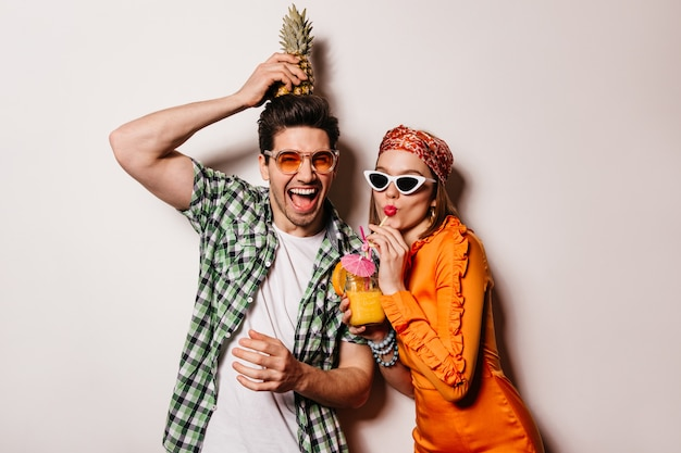 Casal otimista com roupa elegante de verão está descansando e saboreando um coquetel e abacaxi.