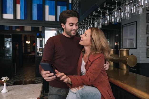 Casal otimista entusiasmado usando o telefone e olhando um para o outro