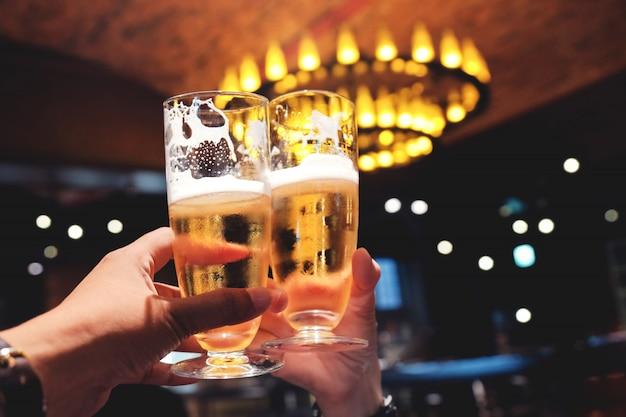 Casal ou amigo fazendo elogios com um copo de cerveja para comemorar