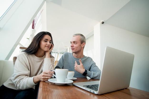 Casal ou amigos estão discutindo um projeto no café. homem atraente sorri, mostra no laptop e diz algo com interesse. casal passando um tempo juntos no café. eles bebem cappuccino.
